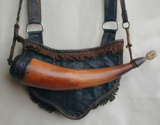 "Randy Hedden PA Bag & HornThis is a small eastern style pouch & horn designed for short hunts or small game hunting.  The pouch measures 6-1/2"" wide X  5"" deep.  Made from veg tanned calf with a 1"" veg tanned pig skin strap.  The horn is 11"" around the outside curve and is 2-1/8"" diameter at the butt.  It features crude concentric ring scrimshaw and a chip carved  cherry butt plug made from a cherry log salvaged from a log cabin built in 1805.   The set also has a river cane powder measure and a wound brass wire vent pick.Photo by Randy Hedden"
