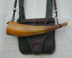 "Randy Hedden Squirrel RigSmall squirrel, or other small game, hunting pouch & horn.  The pouch, made from veg tanned calf, measures 6"" wide X 5-1/2"" deep and the beaver tail flap is lined with brown French linen.  The horn is 8-1/2"" around the outside curve and 2-1/8"" diameter at the red painted butt plug.  the set also features two horn, torpedo type, game hangers, a thirty grain horn powder measure and a wound brass wire vent pick.Photo by Randy Hedden"